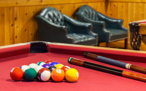 closeup of red billiards table with two black lounge chairs in background