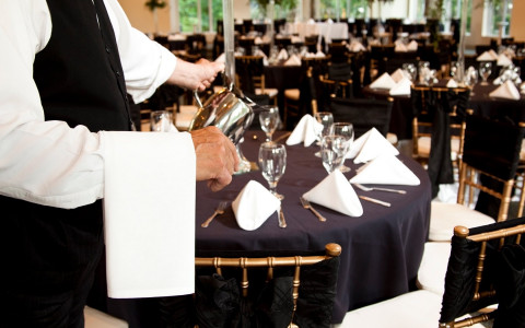 waiter pouring water to tables set up for an event with black tablecloths