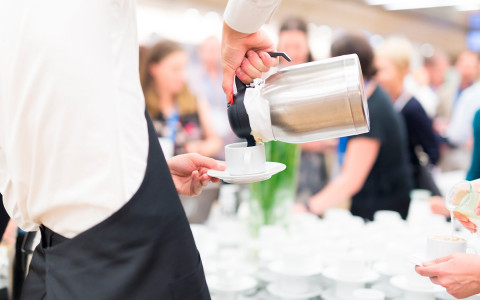 waiter pouring coffee into a white cup