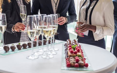 three people in business attire surround a table with champagne glasses and tray of chocolate covered strawberries and mini desserts with fruit