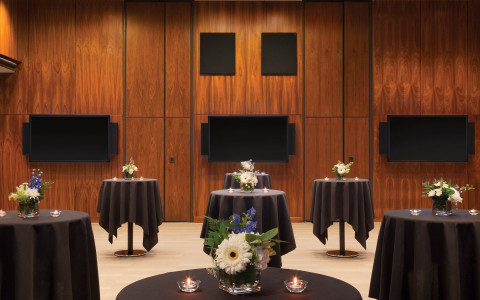 room with cocktail tables with black tablecloth and flowers and candles on top