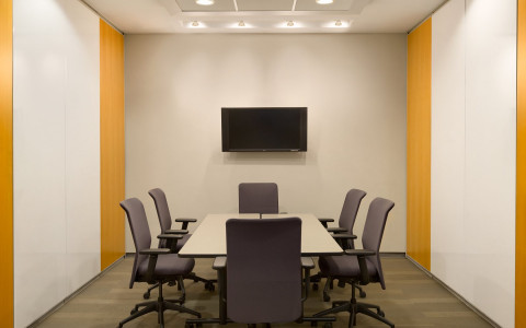 meeting space with a desk and chairs with a tv monitor on the wall