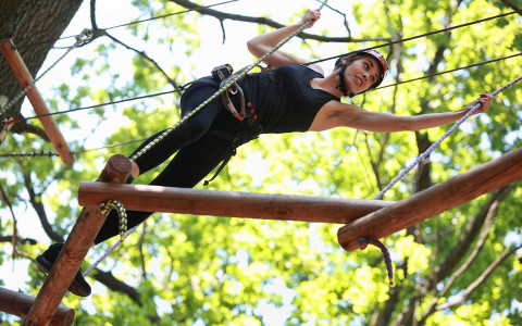 A helmeted woman reaches out to grab a rope high up in the tree canopy