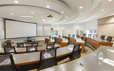 Arced desks with several seats tied down towards a desk with a large projector behind it