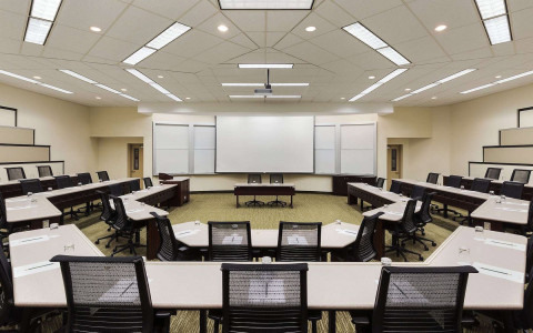 Two rows of octagonal desks surround a presenting desk and a large projector