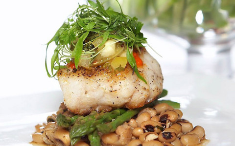 A elegantly plated fish sits over asparagus and beans