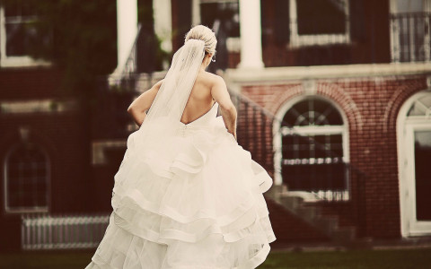A bride lifts her dress to walk towards the entrance of Ivey Spencer