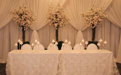 white tables with white table arrangements