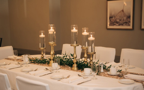 white table with candles and greenery