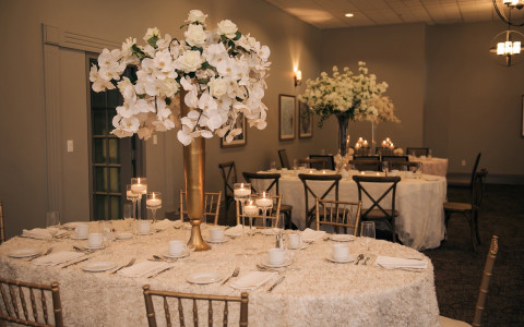 white table cloth with tall flower arrangements