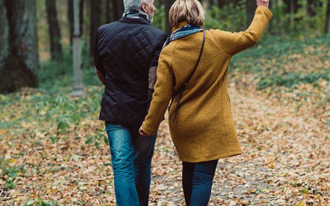 couple in winter clothes walking outside with leaves on the ground