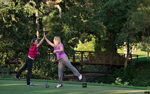two ladies high-fiving while playing golf on golf course
