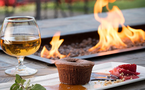 dessert plate with a chocolate souffle in front of a fire pit
