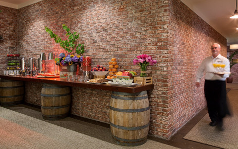 Buffet table with wooden kegs holding it up is set up with flowers, fruit, and baked goods with a brick wall behind the table.