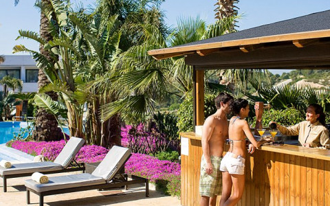 couple buying drinks from outside bar near pool