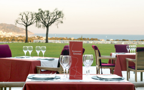 hotels outside restaurant set up with red tablecloths and chairs overlooking grass field and ocean
