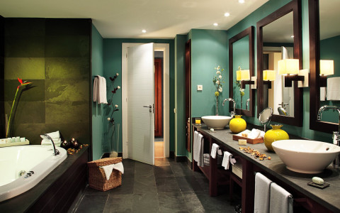 bathroom with blue walls, two sinks, yellow pottery, and bathtub with dimmed lights
