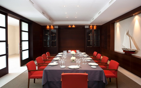 private dining table with set up table and red chairs with a screen is hanging on wall
