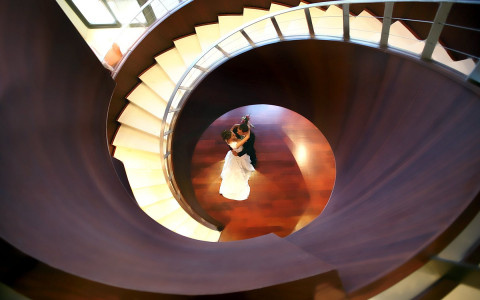 swirled staircase and at the bottom a bride and groom are hugging
