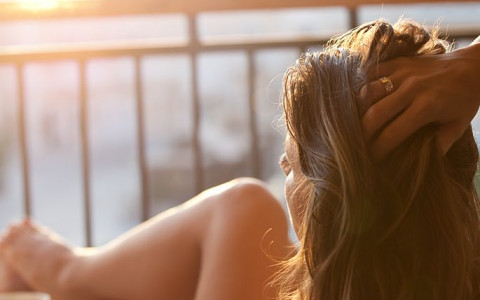 closeup of woman relaxing on her balcony looking at the view during sunset