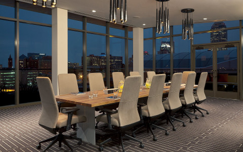 A long wooden conference table is set with tall chairs