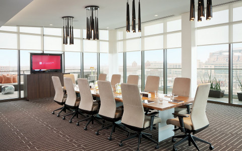 white chairs around a brown conference table