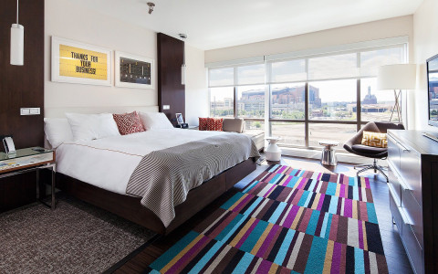 A bed is near a long window with a view of the city and a long artistic rug of various cool tones sits at the foot of the bed