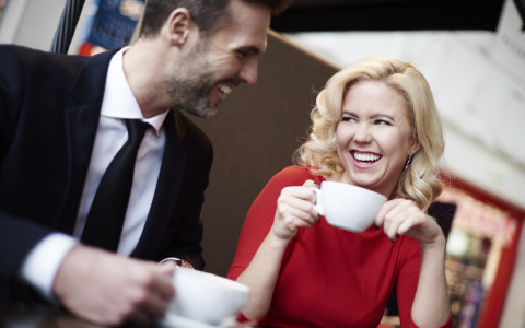man and women drinking coffee and laughing