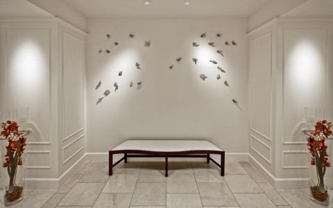 white bench in hall with bird design on wall