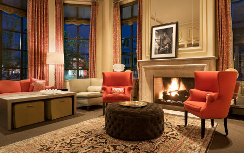 hotel lounge with fireplace and red armchairs