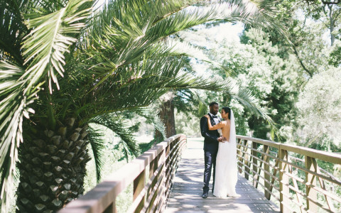 bride and groom posing on a wooden bridge on a sunny day