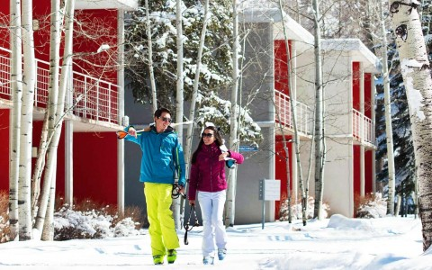 a man and woman walking through the snow with ski gear