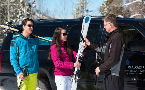 a man and woman holding ski gear outside a car