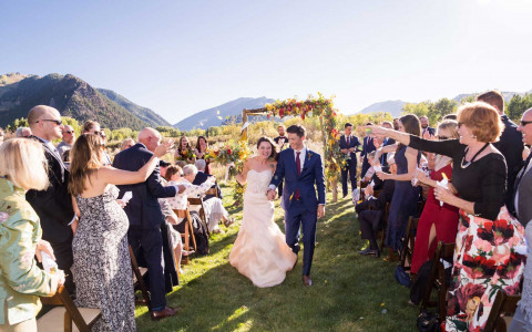 aspen meadows wedding in the summer outdoors with a bride and groom smiling as they walk down the asile