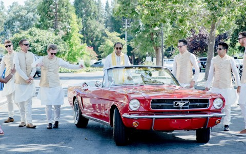 claire barrett photography, Indian wedding groom and groomsmen with a classic red car on their way to the ceremony