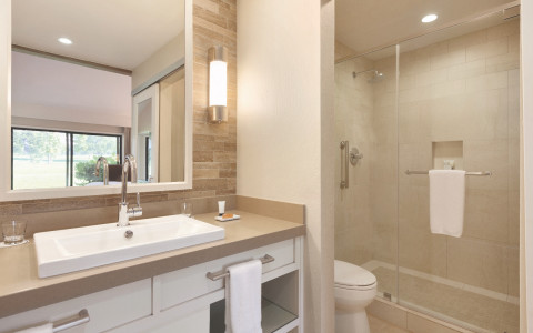 angled view of a cottage resort bathroom with beautiful landscape views of the green