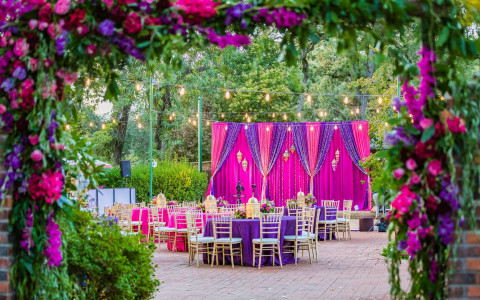 Pink and purple floral stage and table arrangements at an Indian Wedding