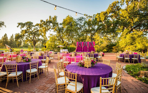 Table and stage setup with a pink and purple theme for an Indian Wedding at one of Silverado's outdoor venues.