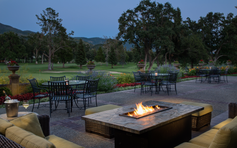 mansion patio overlooking the golf course with outdoor seating and fireplace
