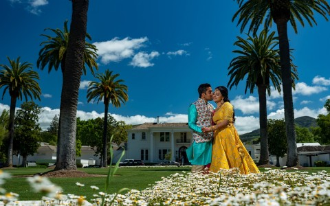 MP Singh Photography LLC, Indian groom kissing bride on the cheek in front of the historic Silverado Mansion on a bright sunny day