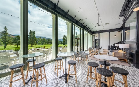 Bar stool seating with floor to ceiling windows that display our golf course.
