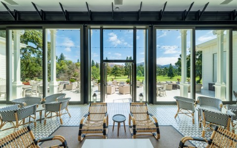 Modern seating inside of the Silverado Mansion's terrace with a beautiful floor to ceiling view of the golf course.