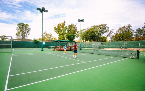 Players outside on the tennis courts preparing for a game