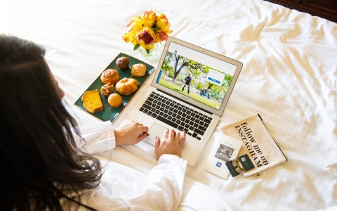 Resort guest visiting the Silverado Resort website while enjoying breakfast pastries in their room