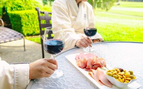 Resort guests sipping red wine with charcuterie out on their resort patio