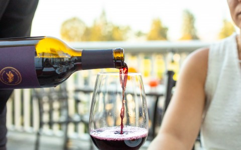 Wine being poured to a resort guest to sip and enjoy out on The Grill patio