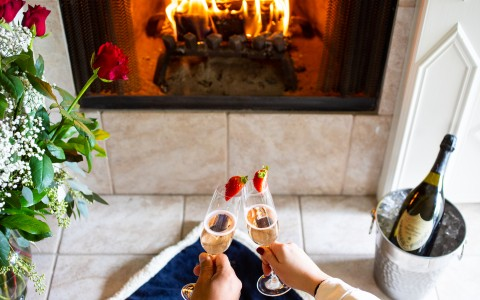 Resort guests spending a romantic weekend at Silverado resort with a bottle of wine in front of the fireplace