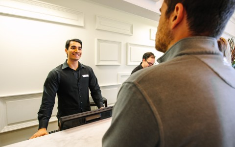 Silverado team member greets and informs guests at the front desk about the iconic Silverado Mansion