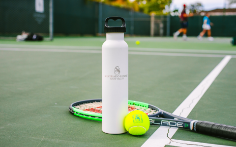 tennis courts with closeup of silverado waterbottle tennis ball and raquet