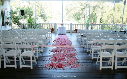 Pink petals scattered down the pathway for a wedding ceremony on fairway deck